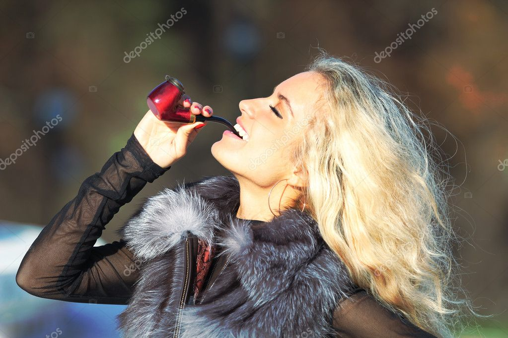 young girl smokes a pipe on the nature stock photo sikora 7651730