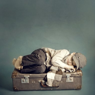 Boy sleeping on a suitcase