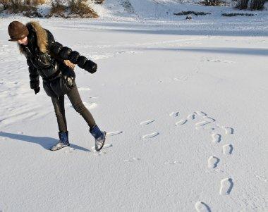 Girl dressed in a black kurta goes, leaving deep footprints in t