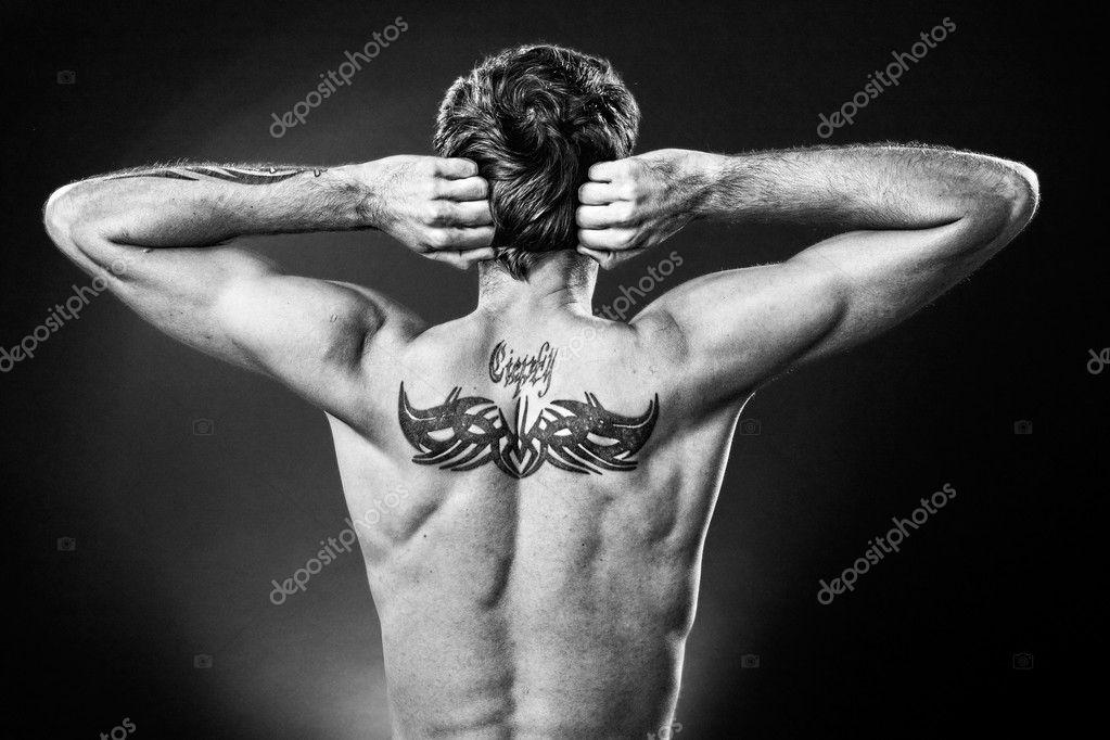 Hombre Mostrando Tatuajes En Su Espalda En Studio Foto De Stock
