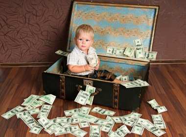 Cute little boy іs sitting in a suitcase with the money