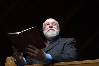 Hansom Senior Caucasian Man Holding a Hymnal in Church Pew