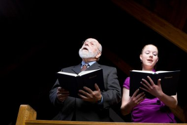 Senior White Man Young Woman Singing in Church Holding Hymnals