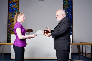 Senior Man Young Woman Holding Wine, Bread, Communion in Church