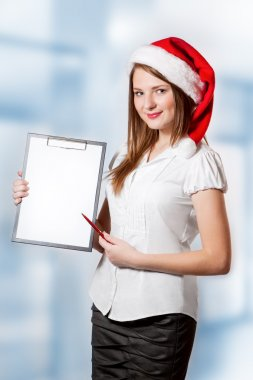 Business woman in Santa Claus hat holds clipboard