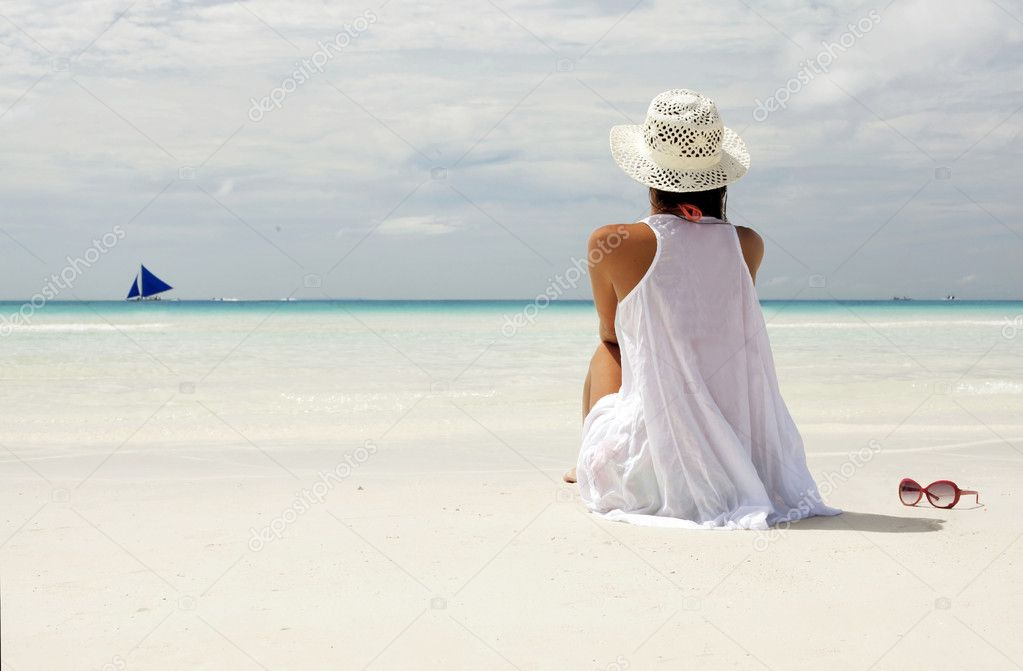 Girl in a hat sitting on the beach and looking on the horizon