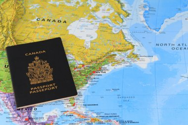 Canadian passport at the map
