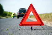 Fotografie Red warning triangle with a broken down car