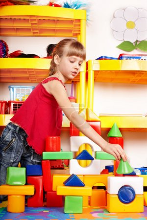 Child with block and construction set in play room. Preschool.