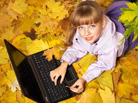 Kid in autumn orange leaves with laptop.
