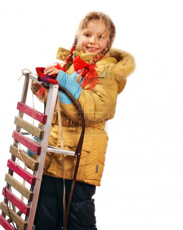 Child holding sleigh on white.