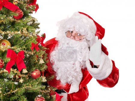 Photo for Santa claus with hand on ear by christmas tree. Isolated. - Royalty Free Image