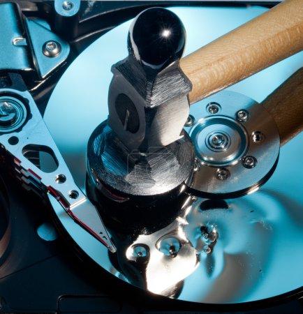 Photo pour Disque magnétique à l'intérieur d'une unité HD d'ordinateur montrant des dommages à la surface miroir des disques magnétiques et lire la tête d'écriture à partir d'un marteau - image libre de droit
