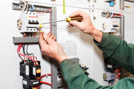 Electrician`s hands working with screwdriver