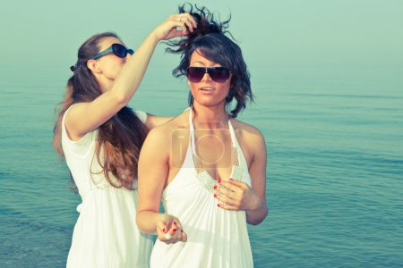 Young Woman Dress Her Friend Hairs at Seaside