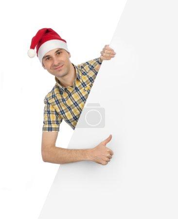 Smiling guy in santa hat with blank billboard