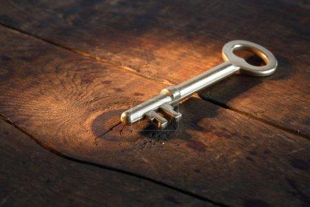 Photo pour Gros plan de vintage or clé couché sur une surface en bois ancienne avec faisceau de lumière - image libre de droit