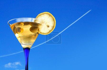 Foto de Concepto de vacaciones. Vidrio Martini contra cielo azul con avión jet volador - Imagen libre de derechos