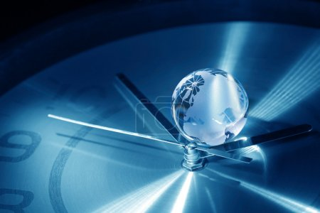 Photo for Time concept. Closeup of glass globe lying on blue metal clock face - Royalty Free Image