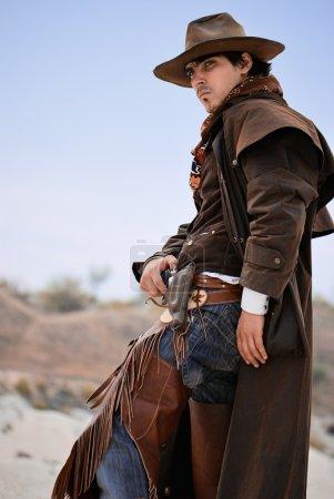 Photo pour Beau cowboy en habillement spécifique avec l'arme. coup de feu en plein air - image libre de droit