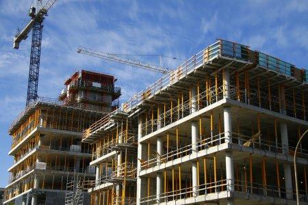 Photo pour Construction de bâtiments avec deux grues sur une belle journée - image libre de droit