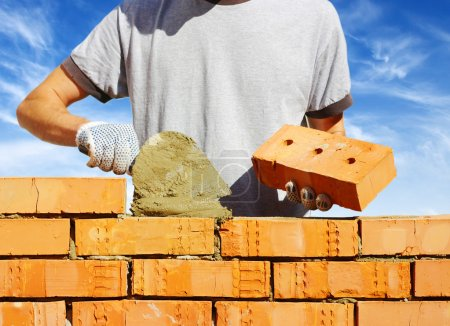Photo for Bricklayer laying bricks to make a wall - Royalty Free Image