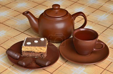 Teapot, a cup of tea, cakes and sweets
