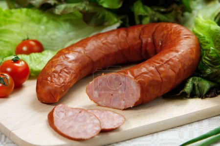 Photo for Smoked sausage on wooden cutting board - Royalty Free Image