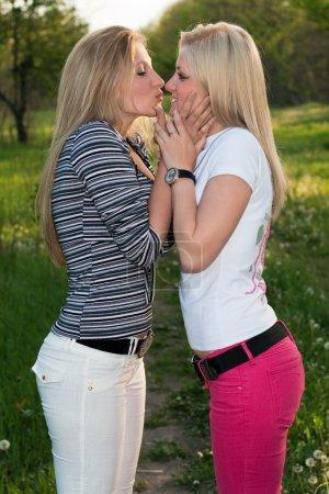 Foto de Retrato de dos rubia juguetona besos al aire libre - Imagen libre de derechos