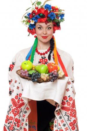 Photo pour Jeune femme dans les vêtements nationaux ukrainiens avec des fruits - image libre de droit
