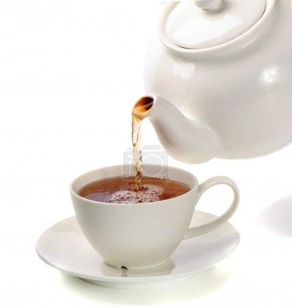 thé versé dans la tasse de thé isolé sur fond blanc