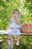 Bambina si siede su una panchina con un cesto di mele