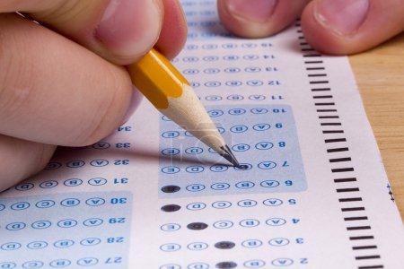Photo pour Étudiant remplissant les réponses à un test avec un crayon . - image libre de droit