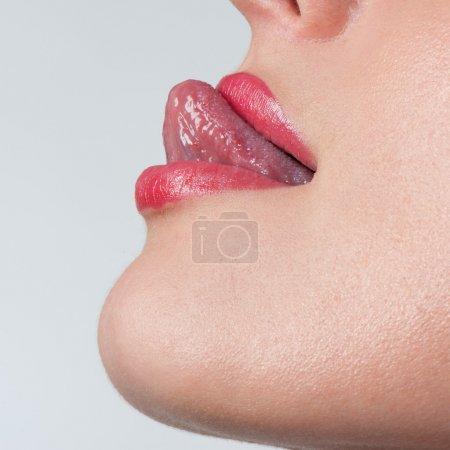 Photo pour Gros plan portrait d'une séduisante bouche semi-ouverte avec langue sexy - image libre de droit