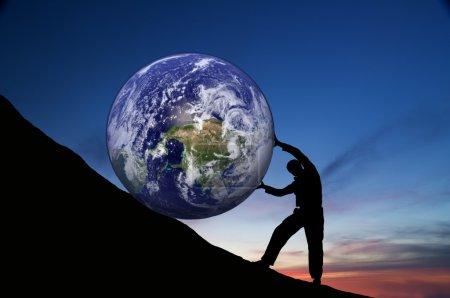 Photo pour Work.the dur personne roule le globe sur la montagne. - image libre de droit