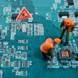 Miniature engineers fixing error on chip of mother...
