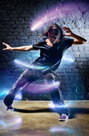 Photo for Young woman dancer. With lights effect. - Royalty Free Image