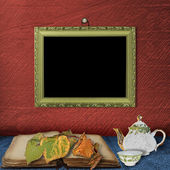 The wooden frame on the wall and teapot with cup of tea on the