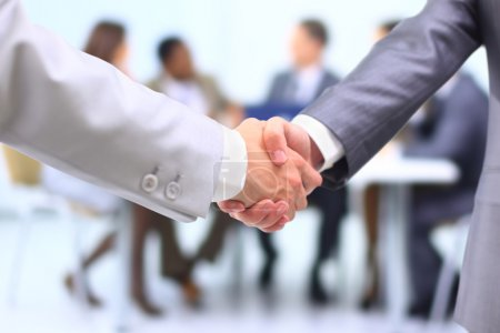 Photo for Two successful businessman shaking hands in front of corporate team at office - Royalty Free Image