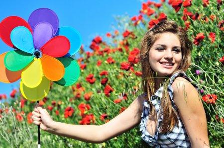 Photo pour Heureux mignon adolescent fille avoir amusant avec moulin à vent sur l 'pavot champ - image libre de droit