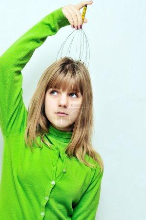 Photo for Teen girl enjoying using head scalp massage - Royalty Free Image