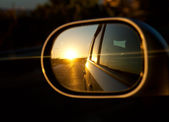 A sunset in the rearview mirror of car as a races down the road