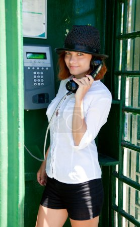 Young woman is standing at phonebox