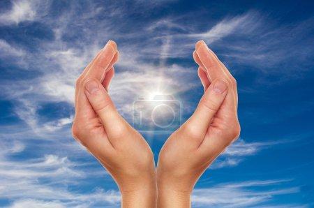 Photo pour Mains féminines sur le ciel bleu avec nuages - concept de protection de la religion et de l'environnement - image libre de droit