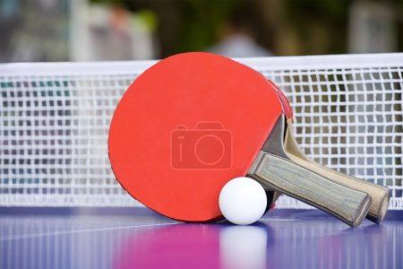 Two table tennis or ping pong rackets and balls on a blue table
