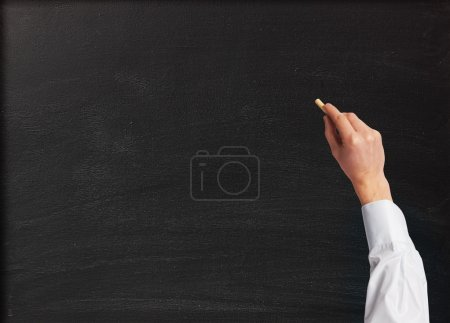 Hand with a chalk against blackboard background