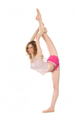 Smiling girl in sportswear does gymnastic exercise