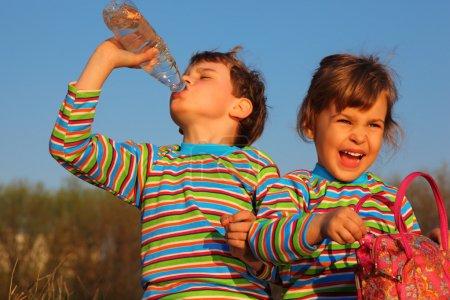 Photo pour Deux enfants en T-shirts rayés, garçon boit de la bouteille, fille tient le sac - image libre de droit