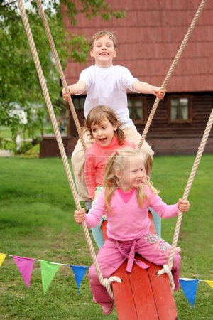 Foto de Tres niños en columpio - Imagen libre de derechos