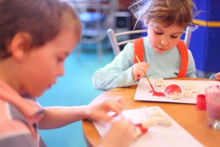 Children paint toys from clay